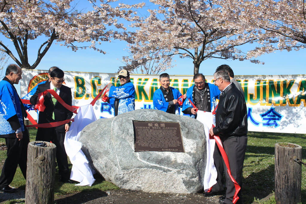 People unveil a stone monument in the Cherry Tree Garden